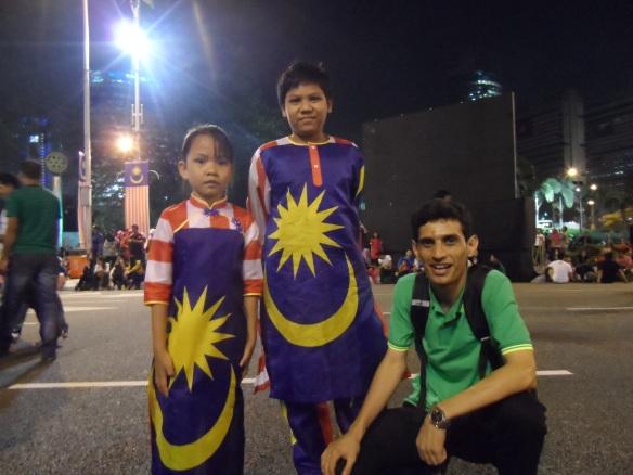 في ميدان الإستقلال في العاصمة الماليزية كوالالمبور مع أطفال ماليزيين يرتدون العلم الماليزي