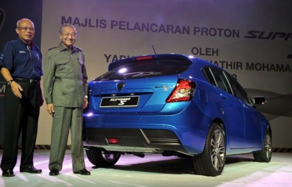 رئيس الوزراء الماليزي الاسبق يقف أمام أحد نماذج السيارات الماليزية.